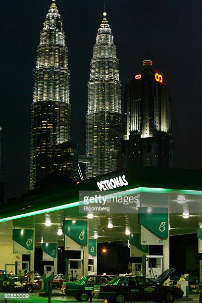 A Petroliam Nasional Bhd signboard is lit up over a gas station near the illuminated Petronas KLCC Twin Towers in Kuala Lumpur Malaysia on Thursday...