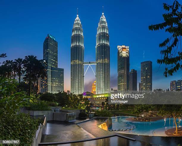 Petrona Towers Kuala Lumpur skyscrapers illuminated at dusk KLCC Park