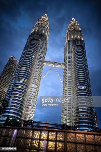 petronas towers by dusk - simetria stock photos and pictures