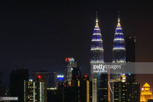 petronas twin towers illuminated in blue lights for solidarity campaign for covid-19 front liners. - shaifulzamri stock pictures, royalty-free photos & images