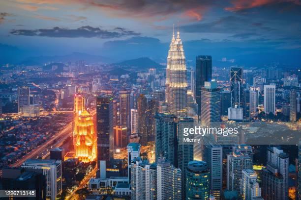 petronas twin towers sunset twilight kuala lumpur illuminated cityscape - malaysia stock pictures, royalty-free photos & images