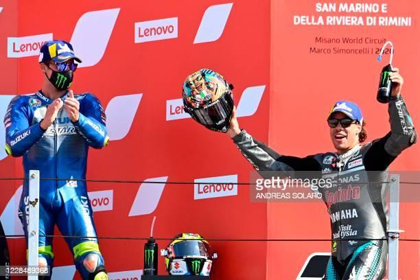 Petronas Yamaha SRT' Italian rider Franco Morbidelli celebrates his win on the podium next to third placed Suzuki Ecstar's Spanish rider Joan Mir...