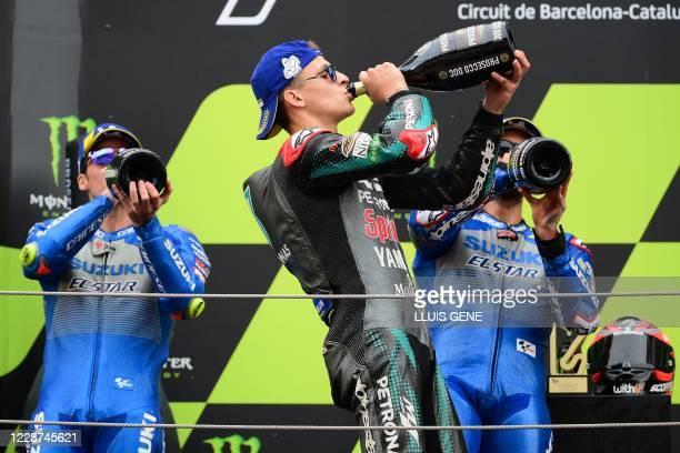 Petronas Yamaha SRT's French rider Fabio Quartararo celebrates his victory with second placed Suzuki Ecstar's Spanish rider Joan Mir and third placed...