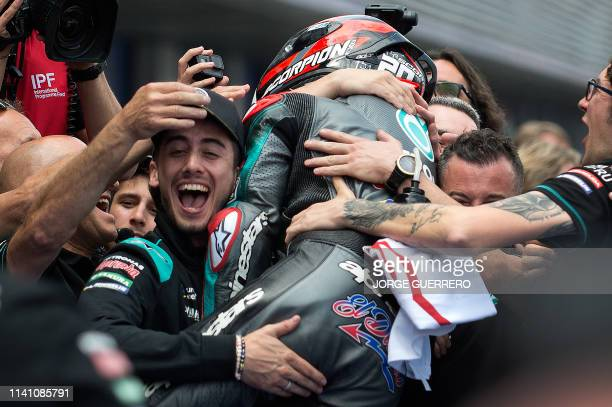 Petronas Yamaha SRT's French rider Fabio Quartararo celebrates with his team after earning the pole position for tomorrow's race during the MotoGP...