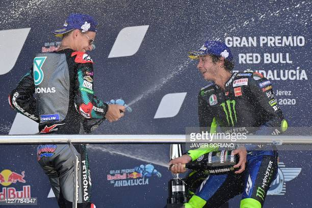 Petronas Yamaha SRT's French winner Fabio Quartararo and Monster Energy Yamaha's third-placed Italian rider Valentino Rossi spray champagne on each...