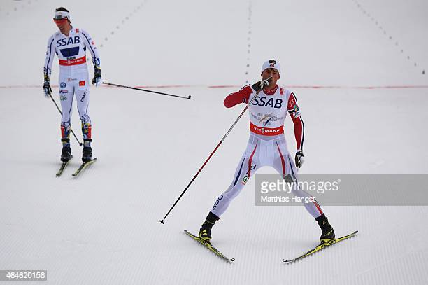 Petter Jr Northug of Norway celebrates winning the gold medal as silver medallist Calle Halfvarsson of Sweden looks on after the Men's 4 x 10km...