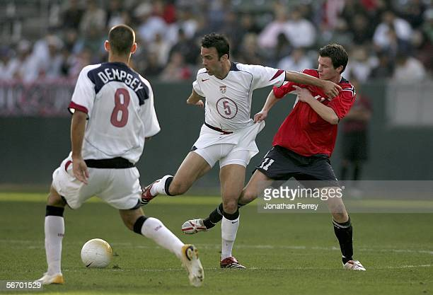 Petter Vaagan Moen of Norway tugs on the shorts of midfielder Kerry Zavagnin of the USA as Clint Dempsey of the USA looks on during an international...