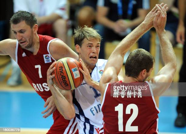 Petteri Koponen of Finland vies with Vitaliy Fridzon and Sergey Monya of Russia during the EuroBasket 2013 Group D match between Finland and Russia...