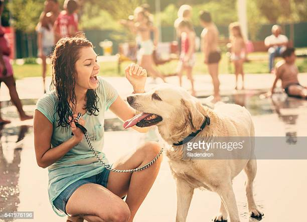 Petting a dog under a fountain