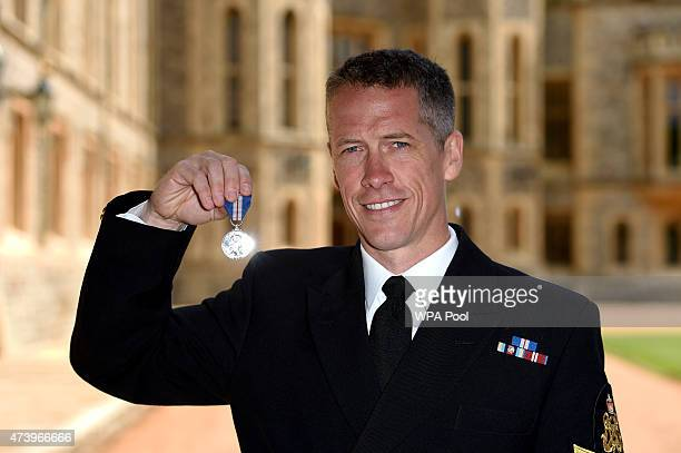 Petty Officer Aircrewman Russell Adams of the Royal Navy with his Queen's Gallantry Medal for great courage in Air and Sea rescue at an investiture...