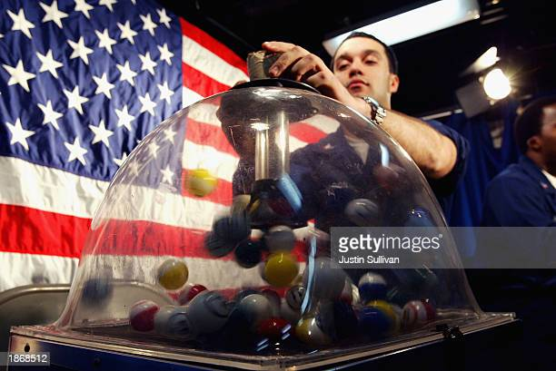 Petty Officer Jose Maldonado of New York City picks a numbered ball during a live shipwide televised broadcast of 'Big Bucks Bingo' on board the USS...