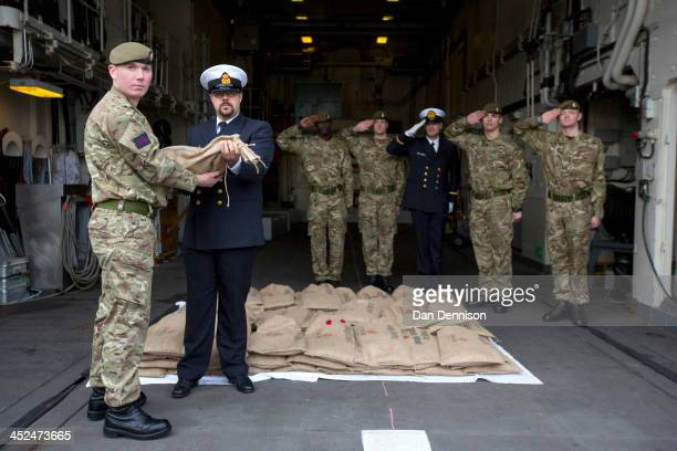 Petty Officer Kevin Ostyn of the Belgian Royal Navy and Guardsman Liam Gaffney of Number 7 Company Coldstream Guards hold a bag of sacred soil from...