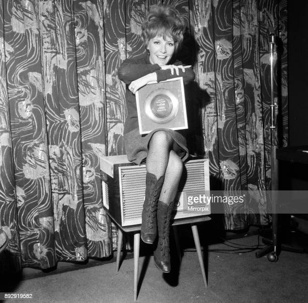 Petula Clark gets a golden disc for 'Downtown', her record which sold a million copies, 1st March 1965.