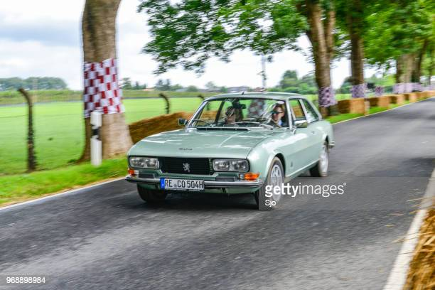 Peugeot 504 Coupe classic car driving on a country road