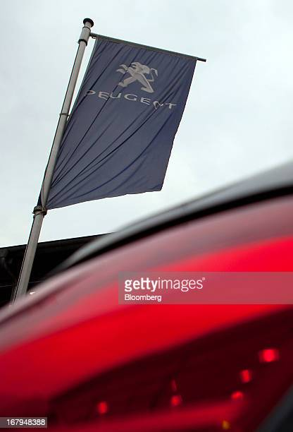 A Peugeot branded flag flies outside a Peugeot auto dealership in Berlin Germany on Thursday May 2 2013 Auto discounts in Germany which accounts for...