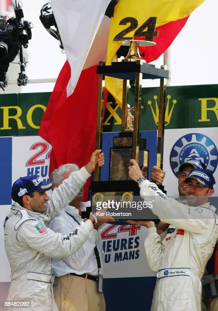 Peugeot Sport drivers Marc Gene of Spain Alex Wurz of Austria and David Brabham of Australia celebrate with the trophy for winning the 77th running...
