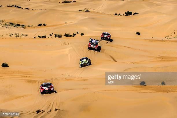 Peugeot team's Sebastien Loeb trails Mini team's Yazeed Mohamed alRhaji and teammates Stephane Peterhansel and Cyril Despres during the 14th special...