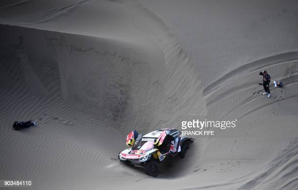TOPSHOT Peugeot's codriver Daniel Elena from Monaco gestures on the ground after getting injured when he and French driver Sebastien Loeb ran into...