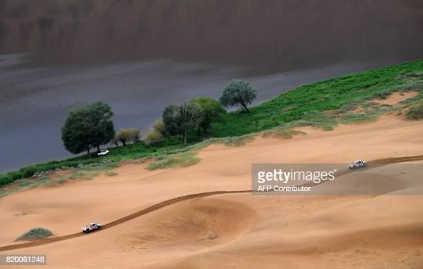 Peugeot's French driver Cyril Despres and co-driver David Castera of France and Peugeot's driver Stephane Peterhansel and his co-driver Jean Paul...