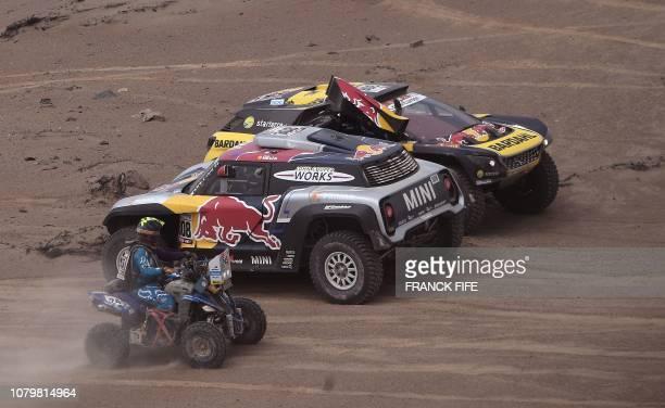 Peugeot's French driver Sebastien Loeb and co-driver Daniel Elena of Monaco and Mini's French driver Cyril Despres and co-driver Jean Paul Cottret...