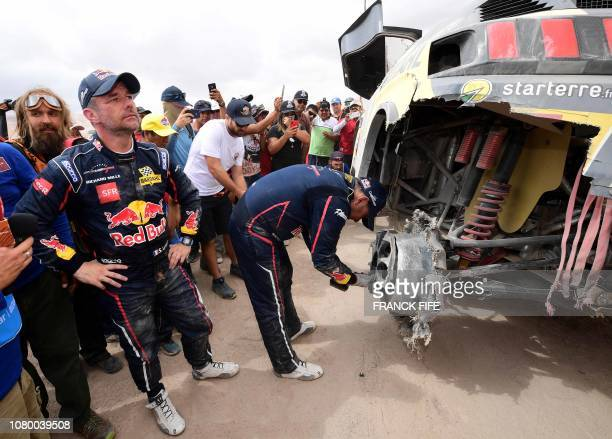 Peugeot's French driver Sebastien Loeb and co-driver Daniel Elena of Monaco check their vehicle upon arriving in Tacna, Peru, at the end of the Dakar...