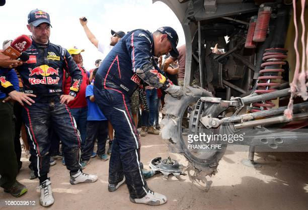 Peugeot's French driver Sebastien Loeb and codriver Daniel Elena of Monaco check their vehicle upon arriving in Tacna Peru at the end of the Dakar...