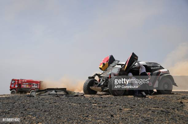 TOPSHOT Peugeot's French driver Sebastien Loeb and codriver Daniel Elena of France check their vehicle during the Stage 9 of the Silk Way 2017...