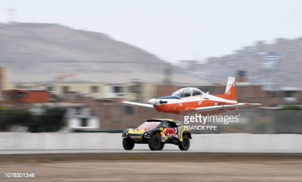 TOPSHOT Peugeot's French driver Sebastien Loeb and codriver Daniel Elena power their car next to a plane before a technical checkup in Lima on 5...