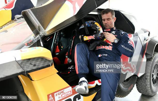 Peugeot's French driver Sebastien Loeb checks his helmet before a driving session on the eve of technical checkup in San Bartolo 75 km south of Lima...