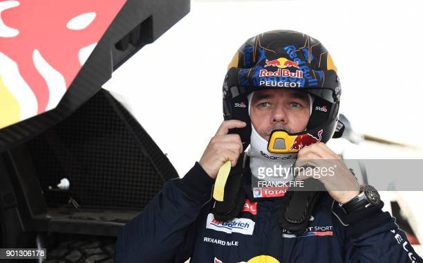 Peugeot's French driver Sebastien Loeb gets ready for a driving session on the eve of technical checkup in San Bartolo 75 km south of Lima on January...