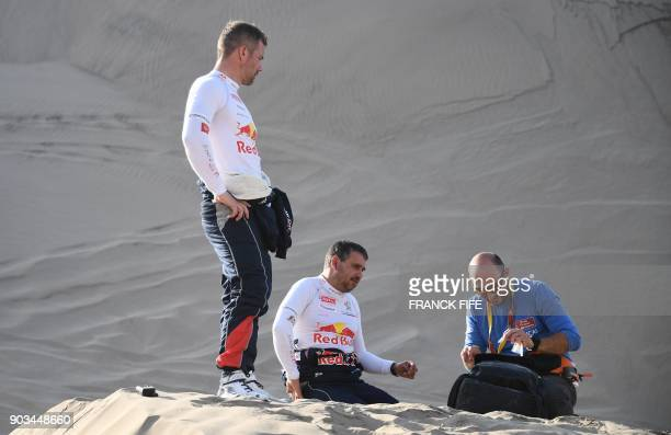 Peugeot's French driver Sebastien Loeb looks on as his codriver Daniel Elena from Monaco is assisted by medical personnel after they ran into sand...