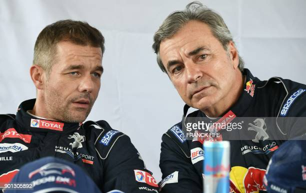 Peugeot's French driver Sebastien Loeb speaks with Peugeot's Spanish driver Carlos Sainz during a press conference before a driving session on the...