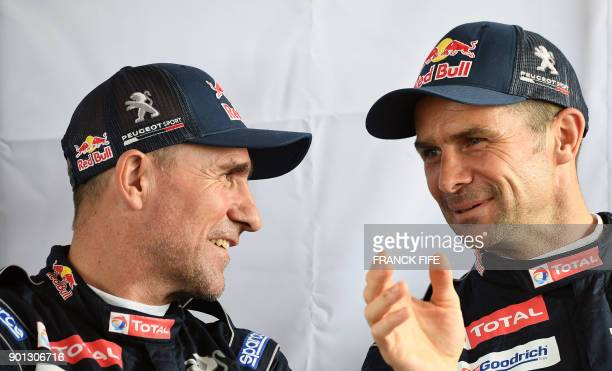 Peugeot's French driver Stephane Peterhansel speaks with Peugeot's French driver Cyril Despres before a driving session on the eve of technical...