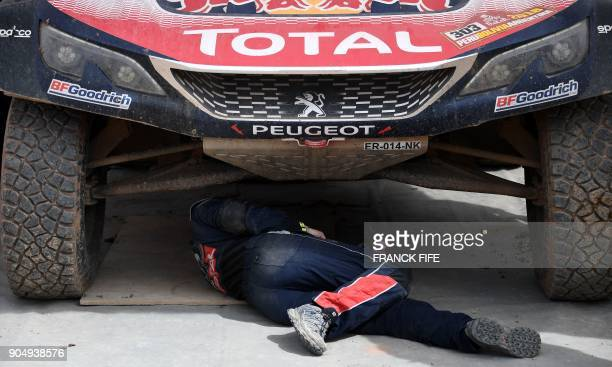 TOPSHOT Peugeot's mechanics repair a car at the end of Stage 8 of the 2018 Dakar Rally between Uyuni and Tupiza Bolivia on January 14 2018 / AFP...