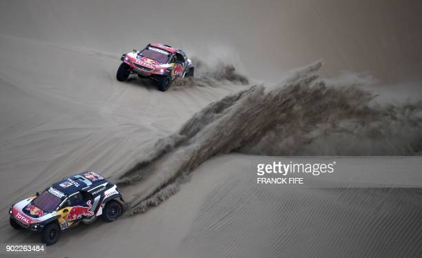 TOPSHOT Peugeot's Spanish driver Carlos Sainz and codriver Lucas Cruz and Peugeot's French driver Cyril Despres and codriver David Castera compete...