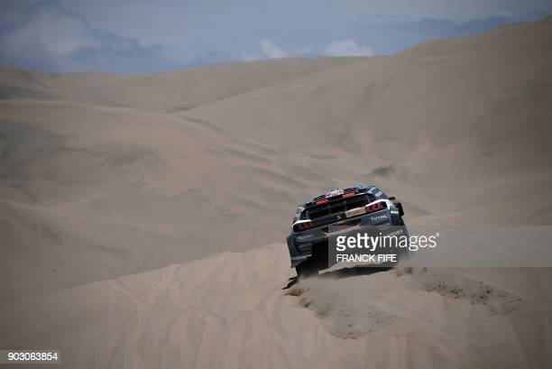 Peugeot's Spanish driver Carlos Sainz and codriver Lucas Cruz compete during Stage 4 of the Dakar 2018 in and around San Juan de Marcona Peru on...