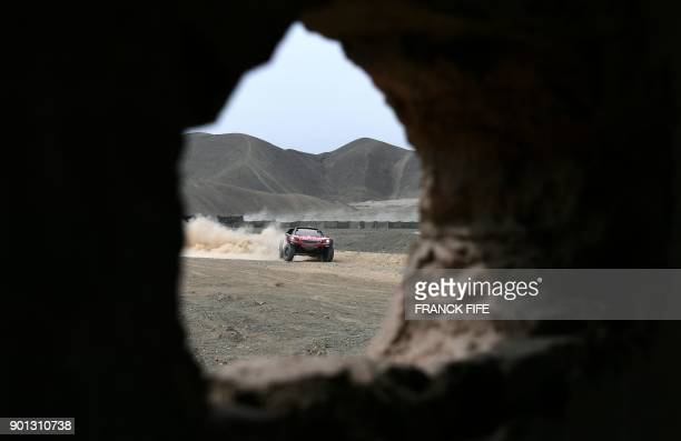 TOPSHOT Peugeot's Spanish driver Carlos Sainz and codriver Lucas Cruz of Spain take part in a driving session on the eve of technical checkup in San...