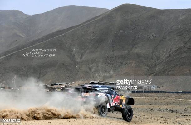 Peugeot's Spanish driver Carlos Sainz and codriver Lucas Cruz of Spain take part in a driving session on the eve of technical checkup in San Bartolo...