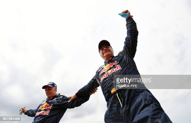 TOPSHOT Peugeot's Spanish driver Carlos Sainz and codriver Lucas Cruz of Spain celebrate after winning the Dakar Rally 2018 at the end of the last...