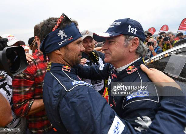 Peugeot's Spanish driver Carlos Sainz is congratulated by his teammate French driver Cyril Despres after winning the Dakar Rally 2018 at the end of...