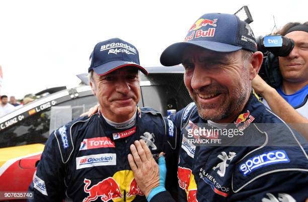 TOPSHOT Peugeot's Spanish driver Carlos Sainz is congratulated by his temmate French driver Stephane Peterhansel after winning the Dakar Rally 2018...