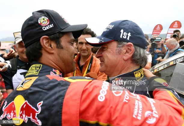 Peugeot's Spanish driver Carlos Sainz is congratulated by Toyota's Qatari driver Nasser AlAttiyah after winning the Dakar Rally 2018 at the end of...
