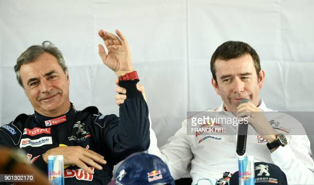 Peugeot's Spanish driver Carlos Sainz jokes with Peugeots team manager Bruno Famin during a press conference before a driving session on the eve of...