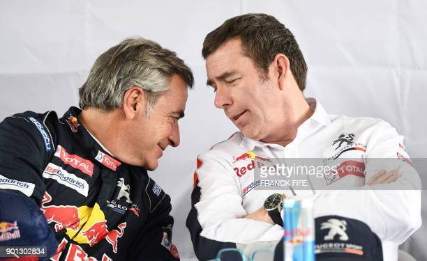 Peugeot's Spanish driver Carlos Sainz speaks with Peugeots team manager Bruno Famin during a press conference before a driving session on the eve of...