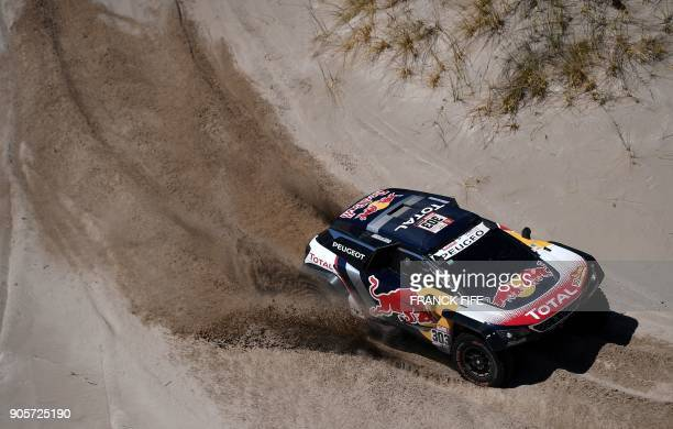 TOPSHOT Peugeot's Spanish drivers Carlos Sainz and codriver Lucas Cruz compete during the Stage 10 of the Dakar 2018 between Salta and Belen...