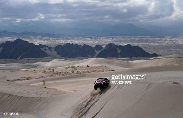 TOPSHOT Peugeot's Spanish drivers Carlos Sainz and codriver Lucas Cruz compete during the Stage 11 of the 2018 Dakar Rally between Belen and...