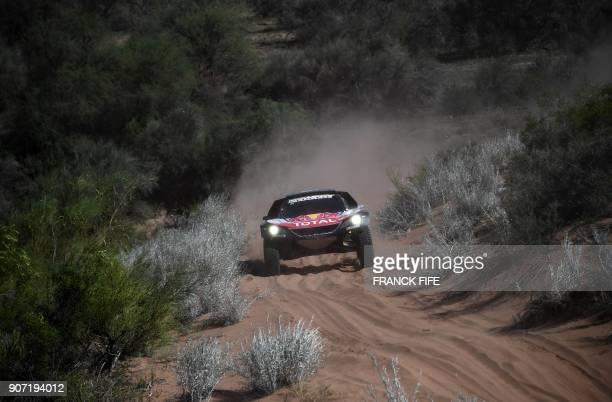 TOPSHOT Peugeot's Spanish drivers Carlos Sainz and codriver Lucas Cruz compete during Stage 13 of the 2018 Dakar Rally between San Juan and Cordoba...