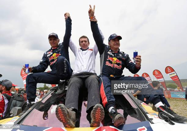 Peugeots team manager Bruno Famin congratulates Peugeot's Spanish driver Carlos Sainz and Spanish codriver Lucas Cruz after their victory in the...