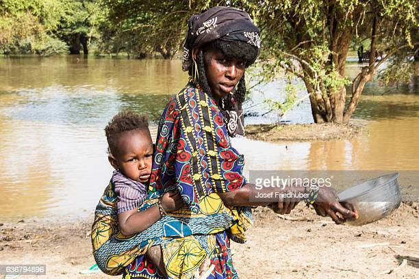 Peul Nomad woman with baby at the water pond.