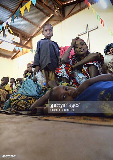 A Peul woman and children take shelter in the Boali church on January 19 in Boali some 100km north of Bangui Fresh fighting broke out in the...